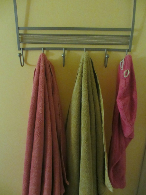 small bathroom storage solution use over-door coat rack as towel hanger